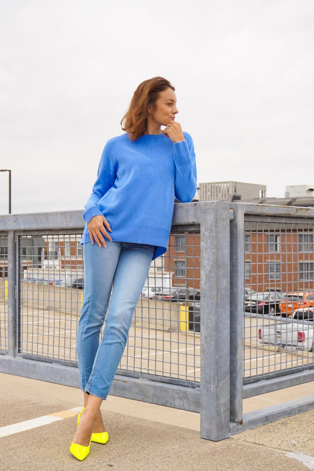 A blogger posing near a fence, wearing a baby blue color sweater, light blue jeans, and neon heels.