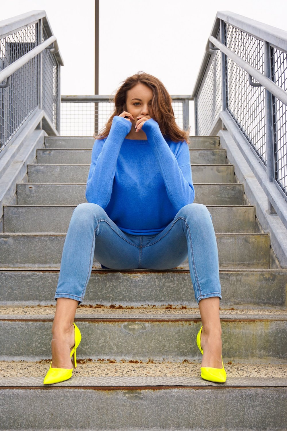 A girl sitting on the stairs, wearing a blue sweater, blue jeans, and neon heels.