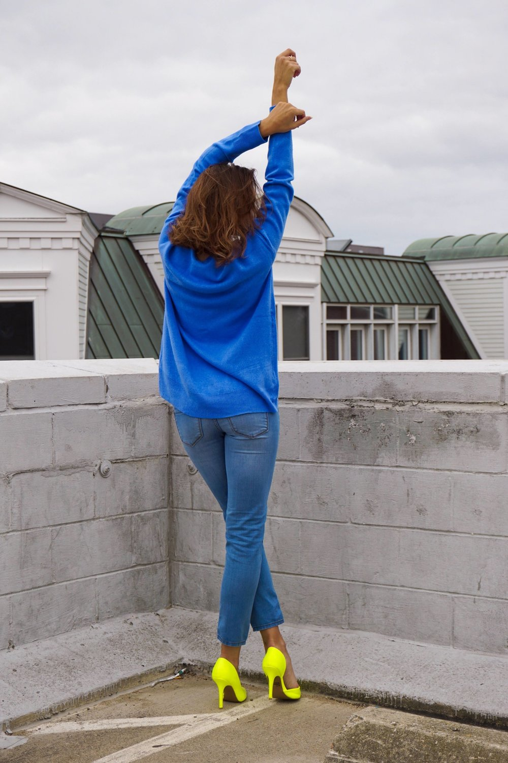A photo of a blogger looking away from the camera, wearing a blue sweater, light blue jeans, and neon heels.