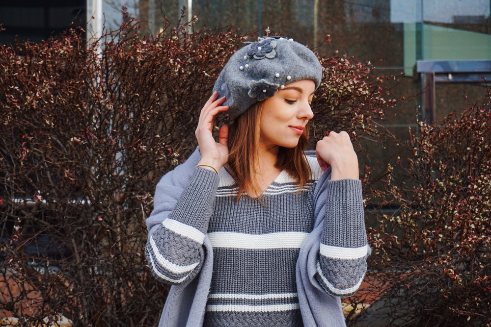 Portrait photo of a fashion blogger looking to her left, wearing a gray and white sweater, gray scarf, and a gray beret.