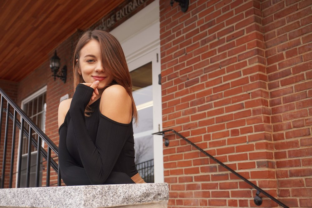 A girl posing in front of a brick building wearing a black shirt with open shoulders.