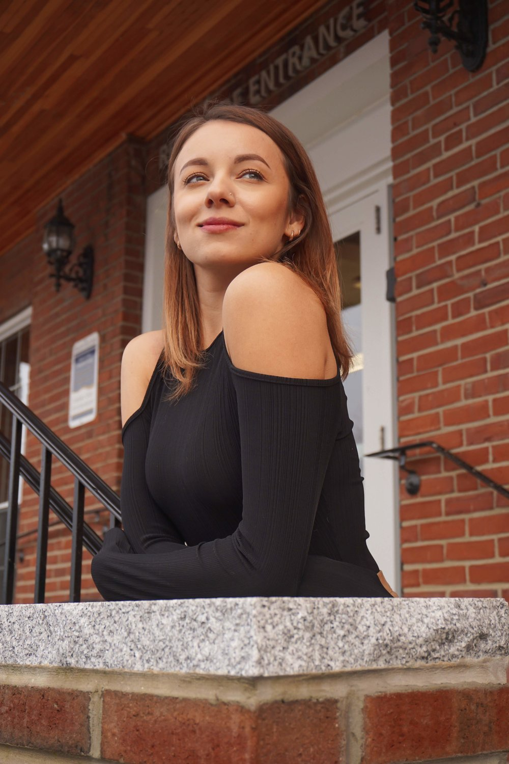 A close-up portrait of a blogger wearing a back shirt with open shoulders.