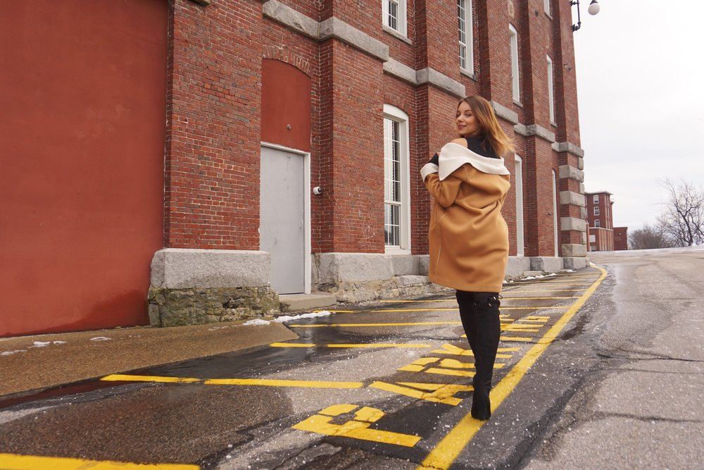 Blogger walking near a brick building, wearing a brown skirt and black over the knee boots.