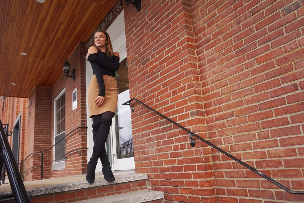 Blogger posing near a brick building wearing a pretty brown and black outfit.