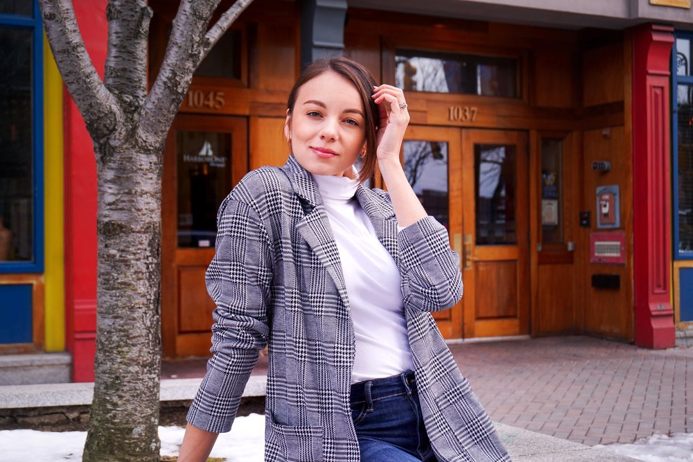 A portrait of a blogger wearing an oversized houndstooth blazer, white turtleneck, and denim jeans.