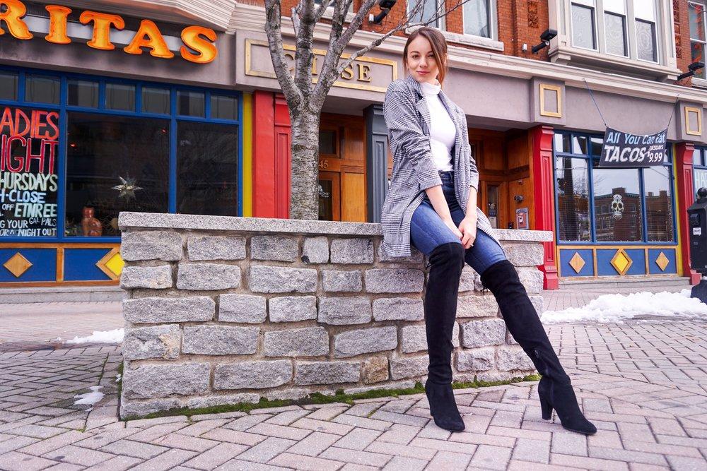 Blogger sitting near restaurants, wearing a houndstooth blazer, white turtleneck, dark denim jeans, and black over-the-knee boots.