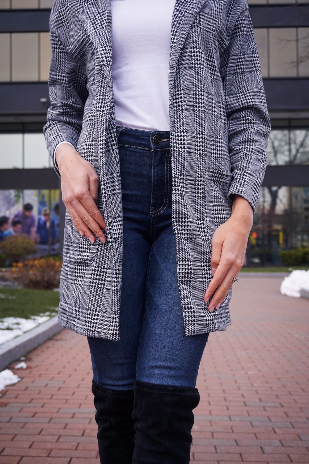 A close-up of a winter outfit: houndstooth blazer, white turtleneck, denim jeans, and black over-the-knees boots.