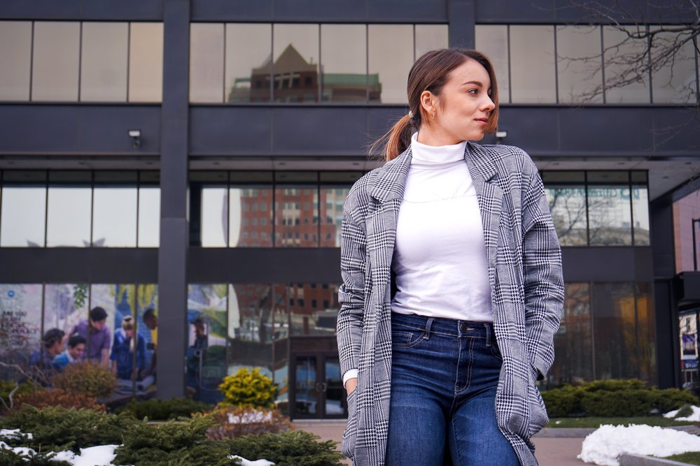 Lifestyle blogger posing in front of a building, wearing a black and white houndstooth blazer, white turtleneck, and denim jeans.