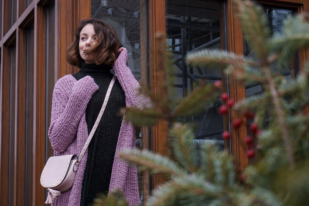 Blogger wearing a pink knit cardigan, green flare sweater dress, black high-knee boots, and pink Victoria Secret bag.