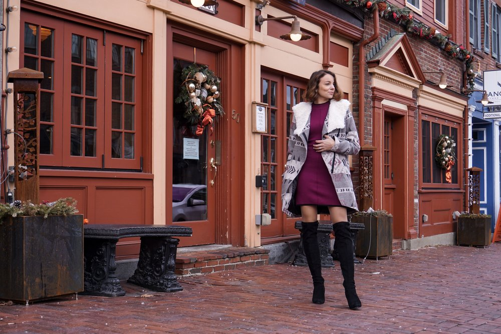 A blogger posing on the street wearing a maroon dress, cozy coat, knee-high boots.