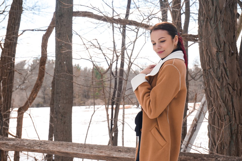 Blogger looking away from the camera wearing a black dress, red scarf on her pony tail, tan colour coat, and black boots.