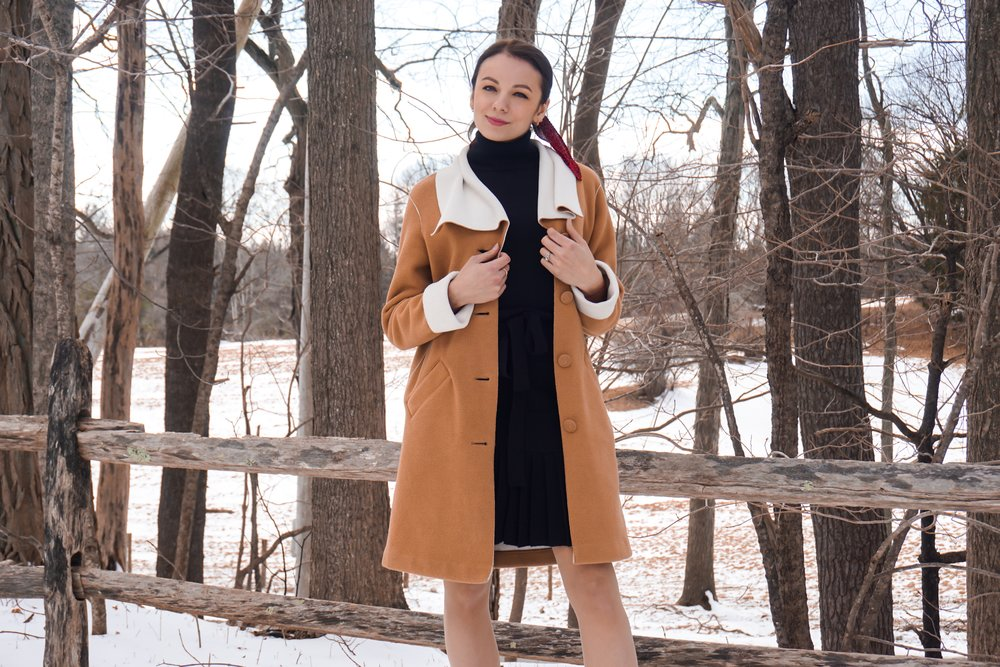 Blogger wearing a black dress, red scarf on her pony tail, tan colour coat, and black boots.