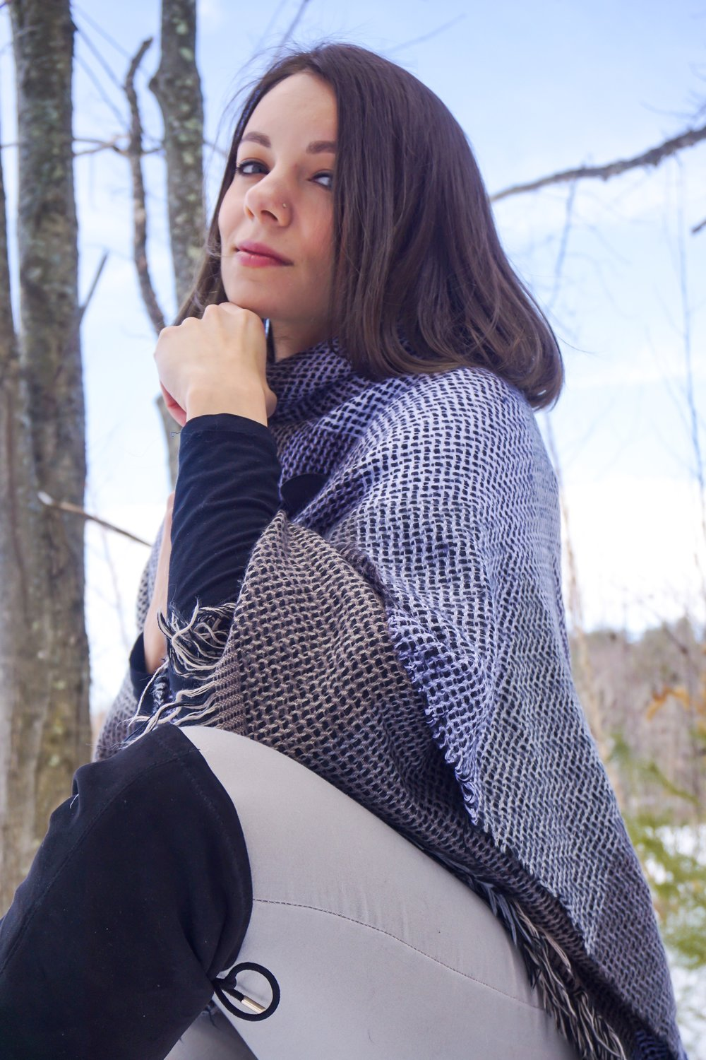 Fashion blogger wearing a warm cozy poncho, black turtleneck, light gray poncho, over the knee boots.