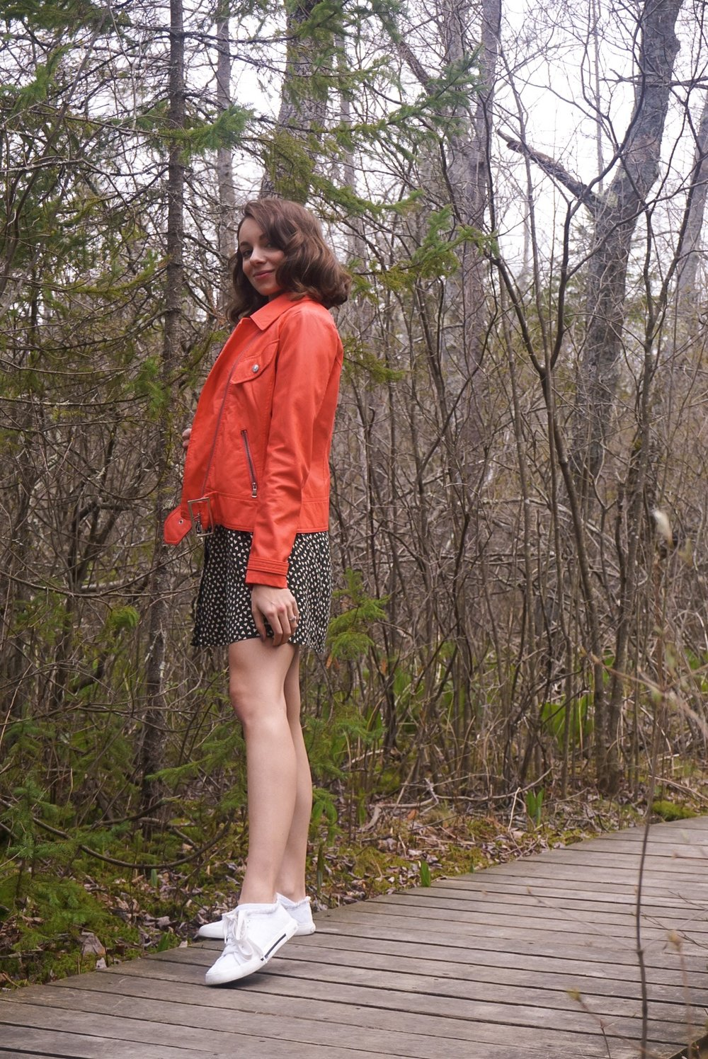 Fashion blogger having a photo shoot in the nature, wearing a dark green short dress, orange faux-leather jacket, and white sneaker.