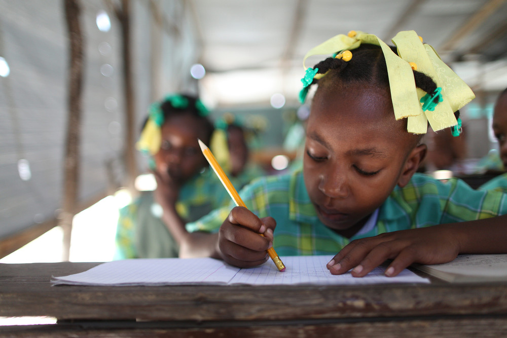 Darose Thamania, 7, does schoolwork as class happens under tarps following the 2010 earthquake. With MCC's support, her school was rebuilt in Croix des Bouquets, Haiti, outside Port-au-Prince.