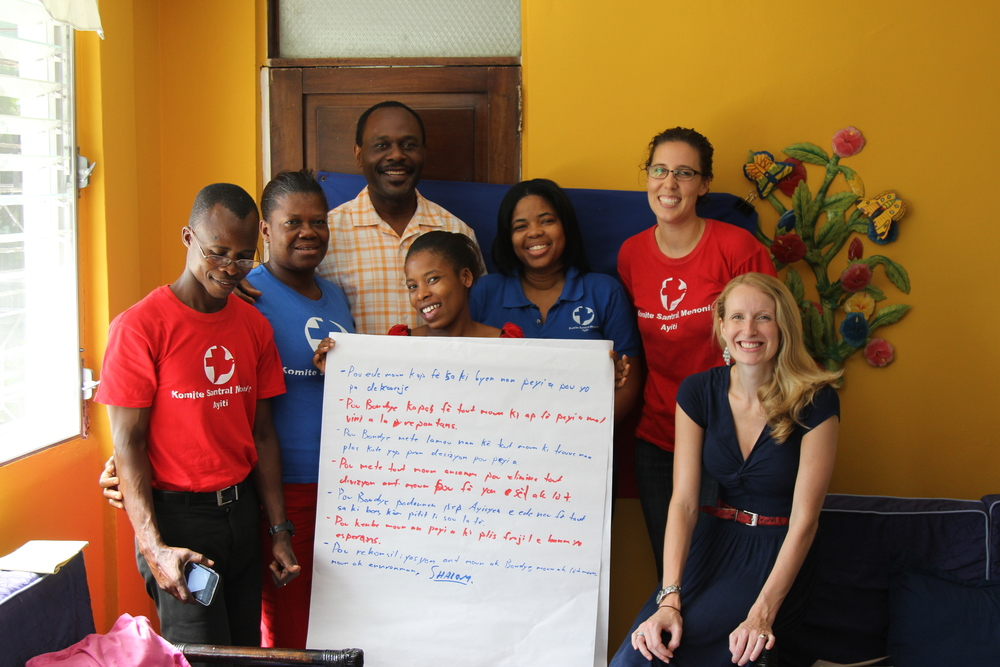 MCC Haiti Port-au-Prince staff: (from left) Joseph, Eclane, Fania (center), Muriel, Katharine, Rebecca with MCC consultant Jose (in back) hold our prayer for Haiti derived from a portion of the Lord's prayer