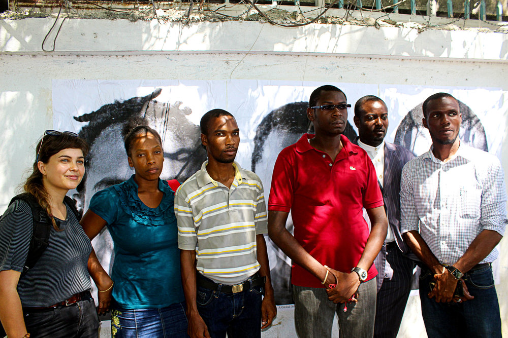 Fellow advocates pose in front of cholera victims' images at the UN log base in Port-au-Prince. Photo credit: Ted Oswald.