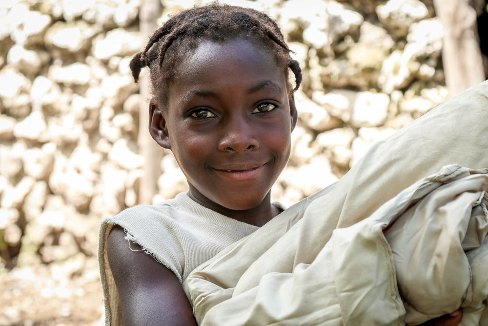Fledana Mezi, 7 years old, holding an MCC relief blanket after the Hurricane -- Biket, Haiti