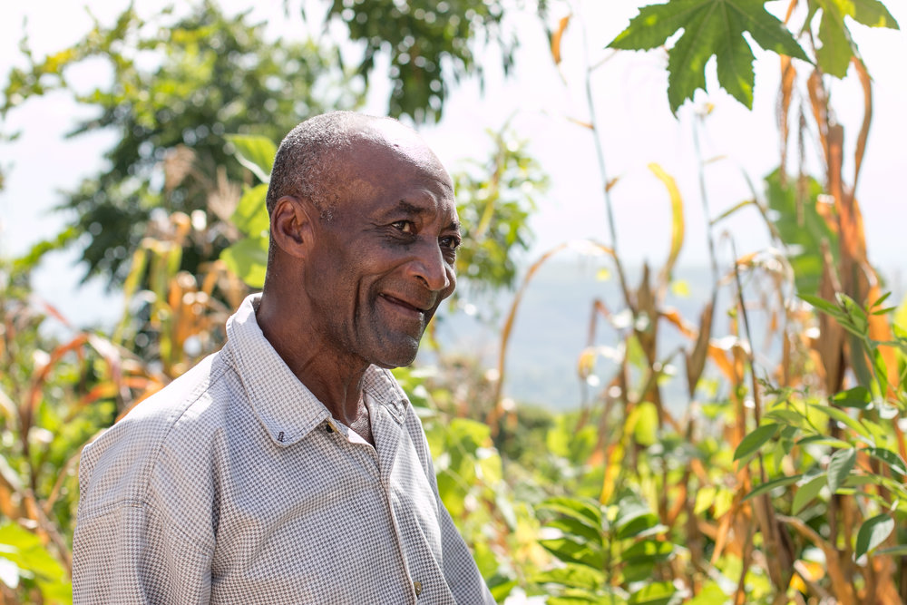 Antoine Calix in front of his garden in the community of Wondo, where MCC helped residents rebuild their gardens after Hurricane Matthew.