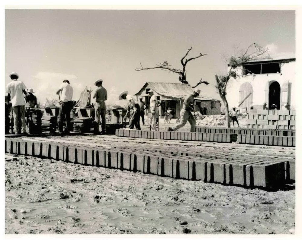 """""""Men anpil, chay pa lou""""—many hands make the load light! Pictured above, cement blocks being prepared for homes."""