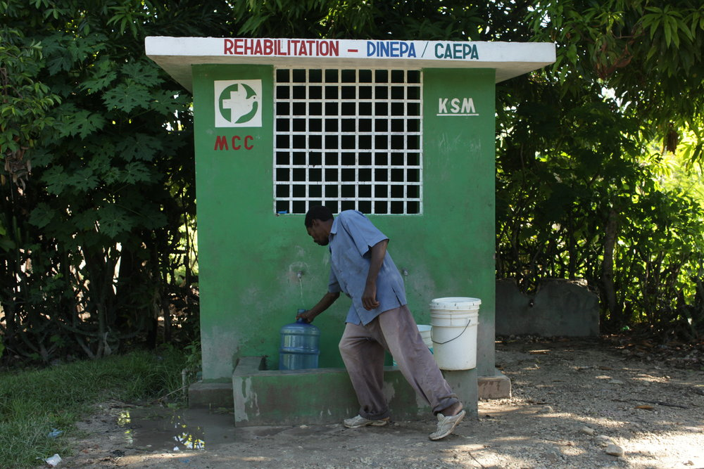 In response to the cholera outbreak and lack of potable water following the earthquake, MCC built 32 kiosks and 11 fountains to provide clean water for residents in and around Desarmes. Pictured above,Germain Isaac waits for his water jug to fill.