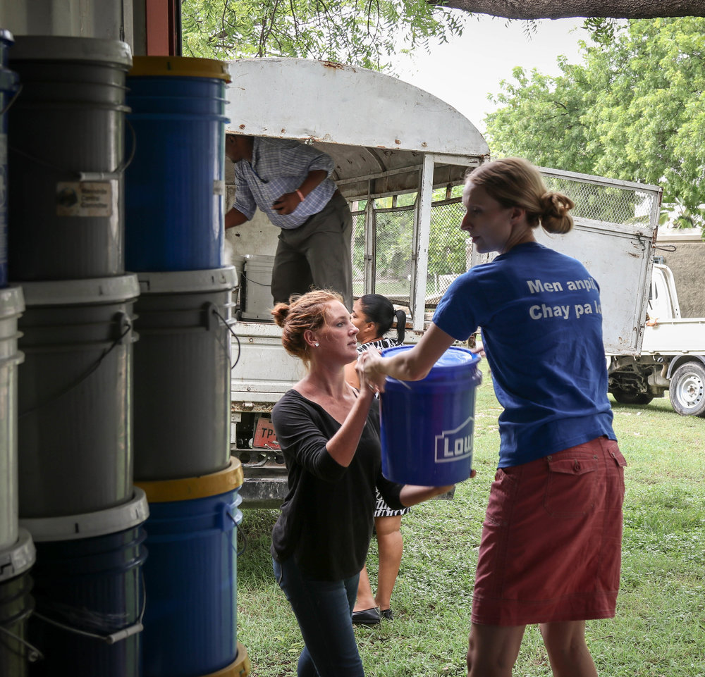 MCC staff loading relief kits, blankets, water purification and canned meat  to members of affected communities.