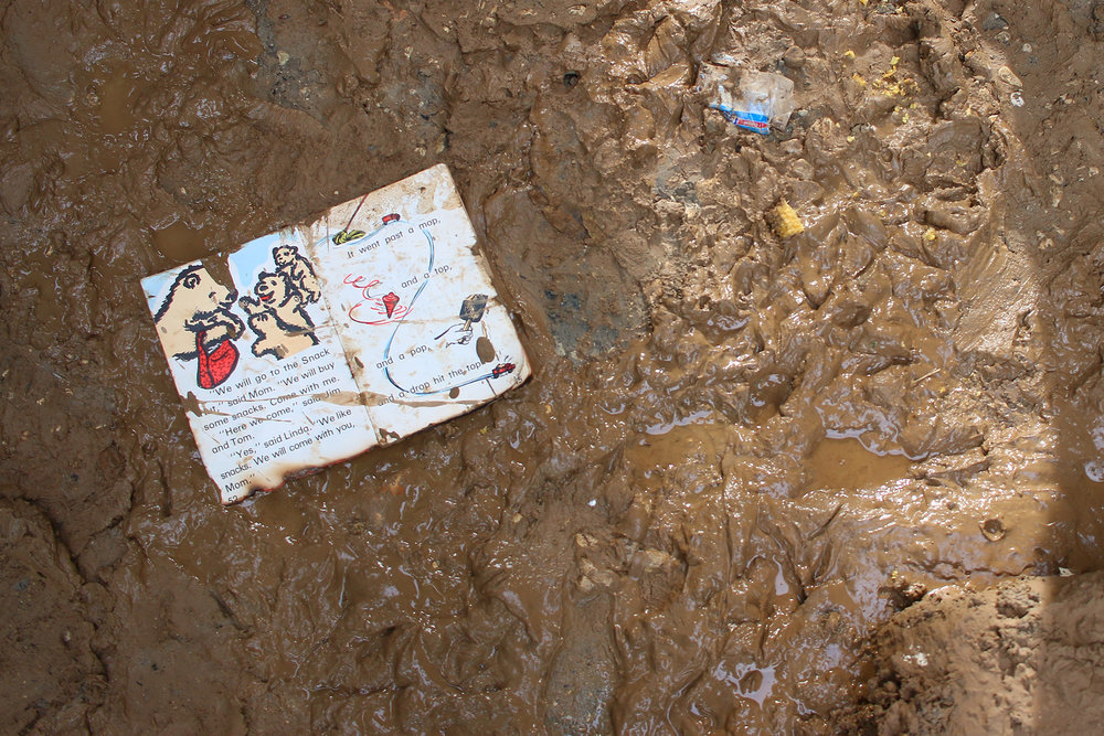 A child's school book is seen in the mud after heavy rains from Hurricane Irma caused flash floods in the commune of Lachappelle, Haiti. Floods destroyed many residents' gardens, which are most households' primary source of income. Without this income, residents may have to pull children out of school or forego medical care because they are unable to pay the fees.