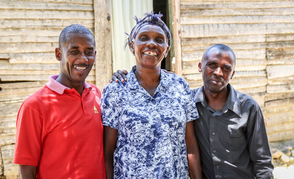 Noel Derenis (center), who has major depression, stands outside her home in Lahoye, Haiti, with her team of community mental health workers Joseph Benissois (left) and Saint-Hilaire Olissaint. They work with MCC partner, Zanmi Lasante, which provides mental health services that have helped Derenis to regain energy to care for herself and her family. MCC photo/Paul Shetler Fast