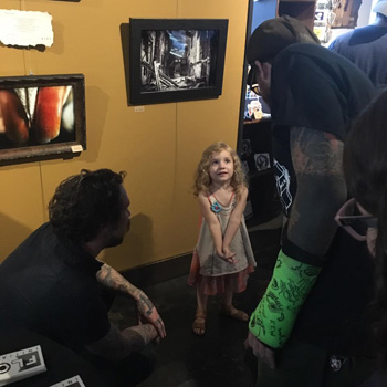 Sean Herman, his daughter Olivia and Dusty Norris. Photo from the recent Skateboard Art Show to benefit the Flow Intitutive at Serpents of Bienville