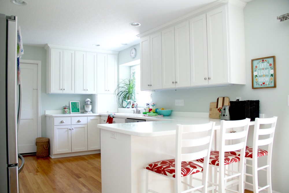 White Kitchen with Shaker Style Cabinets and Warm Wood Floor