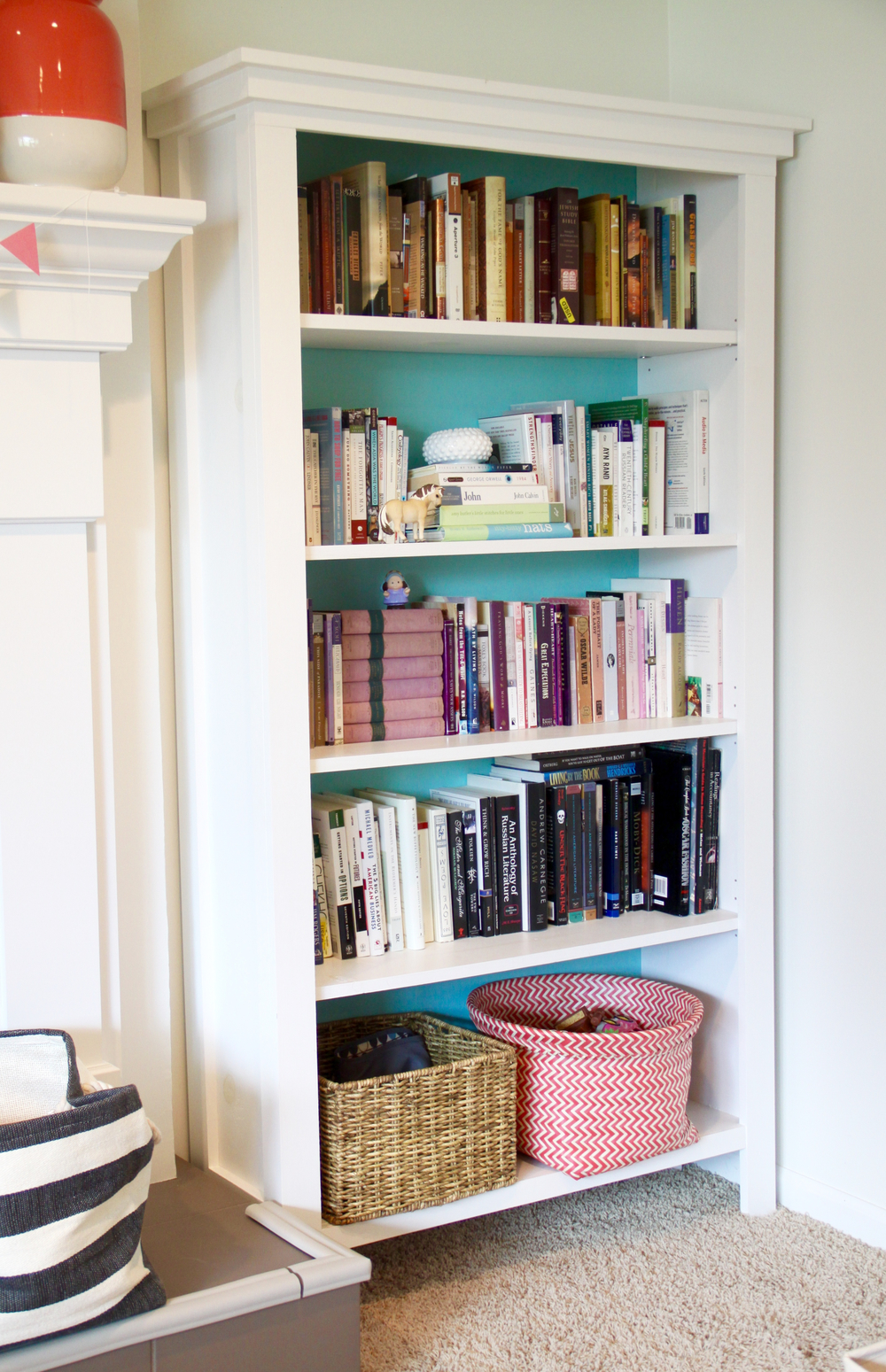 Bookshelves Arranged by Color with Storage Baskets