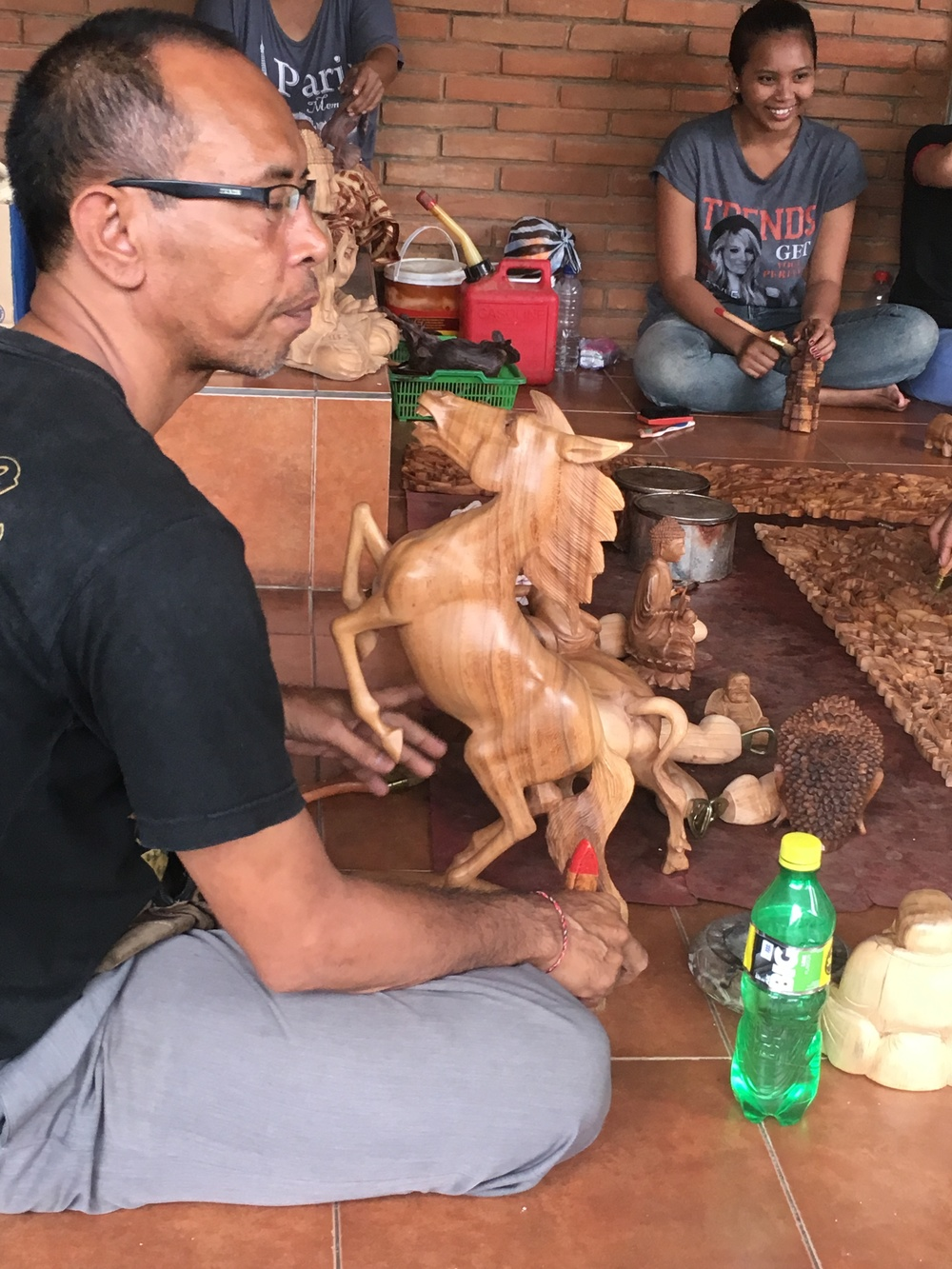 A man carving a horse out of maple wood.
