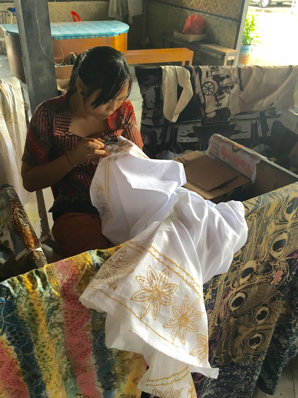 A Balinese woman drawing wax designs on fabric before she paints them.