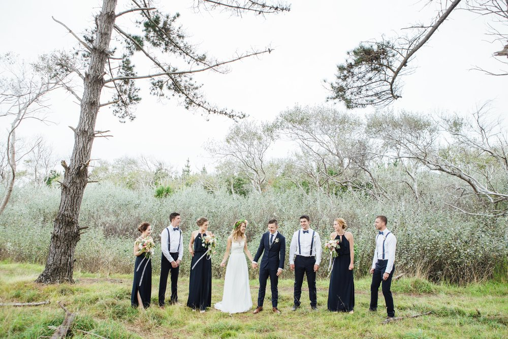 Group shot at Murawai beach | Astra Bride Emma | Upper Room Church | Maggie Sottero Melinda | Wonder Ferris photography |
