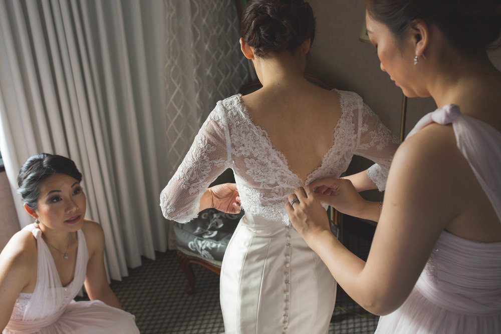 Melissa Boon getting help from her bridesmaids to dress on her wedding day. Photo by Kenrick Rhys