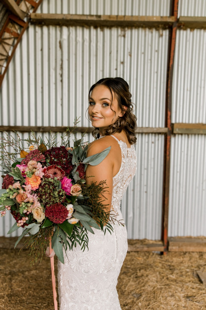 When a team of incredibly talented people get together, something AMAZING happens... - Which is exactly the result of this shoot on a farm in Matamata, with corrugated iron barns and the Kaimai range looming over the background. The dusky pink and muted pallette alongside the gold accents and jewel toned florals make us swoon... Our Sottero & Midgley gown 'Zayn' fit beautifully into this dream-like setting, with its allover lace, delicate boho feel and stunning illusion front and back. The detailed styling of Mellissa from The Styled Table, is utterly fabulous and brilliantly captured by the wonderful Emma from Sweet Events Photography.