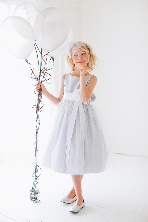 #4 - Ivy - An adorable satin dress overlaid with tulle with a tank top bodice and a wide band of metallic lace at the waist topped with a bow to match the dress.