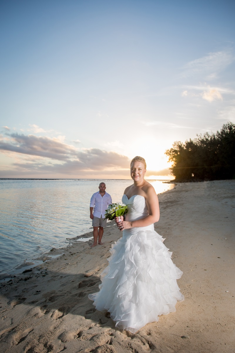 "- We loved Abbey and Jarred's family orientated wedding at Rarotongan Beach Resort and Spa. At a gorgeous beach resort like this, why not encorporate a family holiday into it!Abbey looked an absolute vision in our gown by Mary's Bridal '3Y215.' Those stunning white ruffles floated along the white sand and blended beautifully with the island hues. ""I loved everything about my gown. It was comfortable and I loved the way that it made me feel slim and pretty, haha!""We wanted our day to be family orientated and casual. We didn't have bridesmaids or groomsmen. We chose to have our Daughter Riley (1 yr) and Niece Mishka (6yr) as our flower girls and Nephews Finlay (4) and Jackson (3) as page boys. The best part was when we has our first kiss as husband and wife, the kids were building sand castles at our feet. Couldn't get more casual than that!"