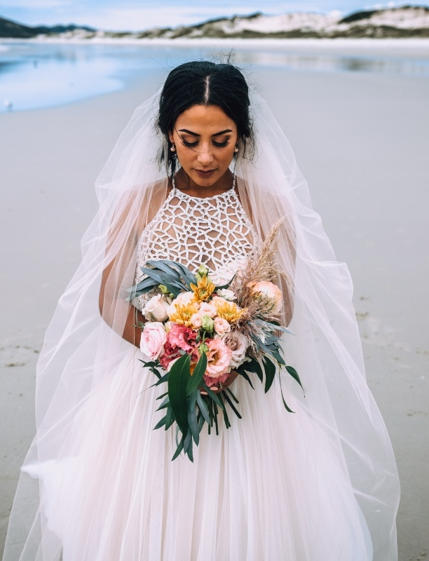 """- A stunning Northland beach, a dashing man and a drop dead gorgeous boho bride make for the most beautiful photos you have ever seen!Carly chose our stunning two piece gown by Sottero & Midgley: the Jude Bodice paired with the Shardea Skirt which created a beach princess look that Carly pulled off beautifully.""""My favourite part of the gown was that it was two piece! It was described as a modern beach princess dress! 100% me and so comfortable!""""Once again, the amazing photography skills of Greg Campbell show through and display his absolute genius behind the lens!"""