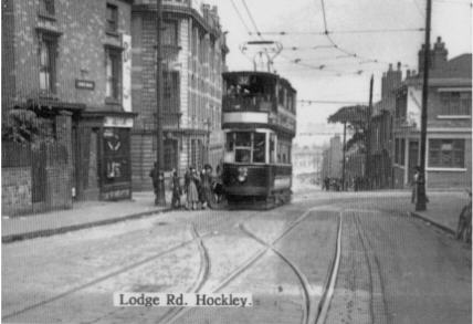 "No 32 tram in Lodge Road Hockle y  after having just left Winson Green, about to turn right into All Saints Street Brookfields with Goode Street Hockley and Scribbans's Bakery on left and ""The Flat ""shopping area straight ahead ."