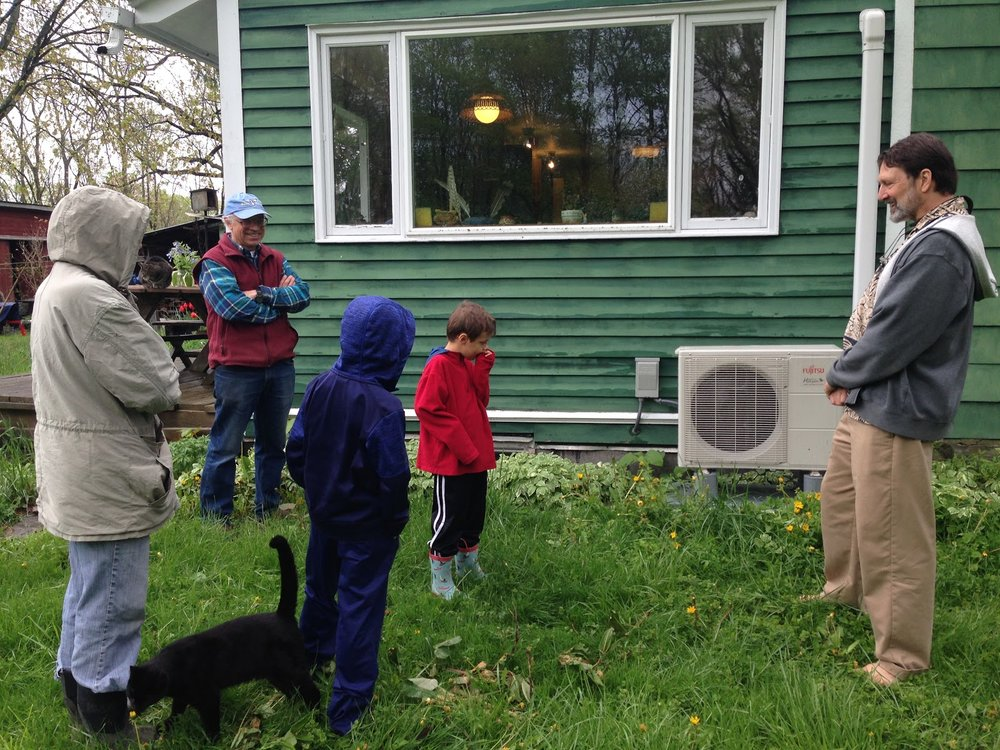 Tom showing the heat pump's compressor unit to a family visiting during a Heat Smart tour; Heat Smart Tompkins coordinator Jonathan Comstock is on right. Photo: Karim Beers