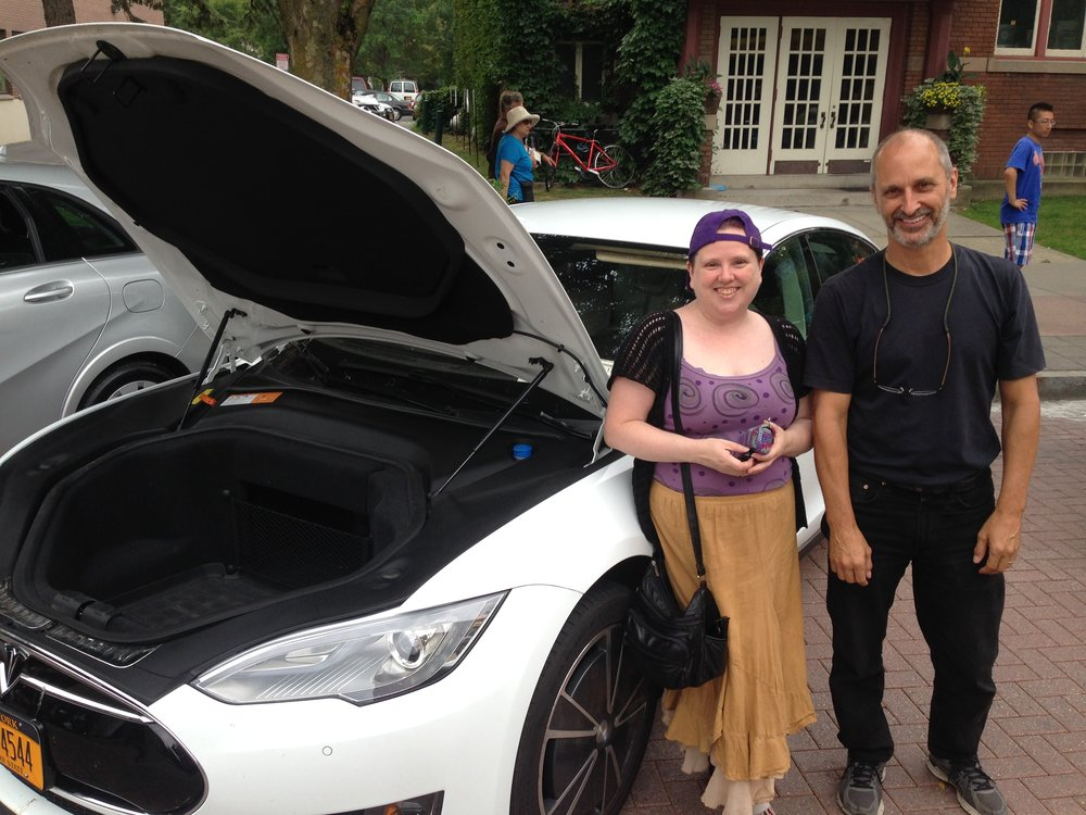 Wait, where did the motor go! Two happy all-electric vehicle owners at a Drive Electric event in Ithaca in 2017 (photo: Karim Beers)