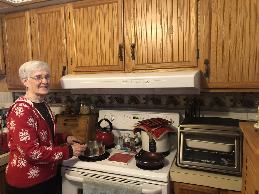 Fran poses with her new stove hood that she received as a part of her participation in New York State-funded energy programs! (Photo: Maggie McAden)