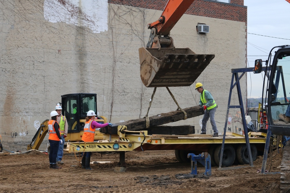City of Alexandria archeologists and conservators from the MAC Laboratory secure 12 foot sections of the warehouse beams onto a flatbed trailer for transportation.