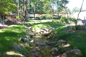 After: Channel bed was raised to reconnect to the floodplain using a reinforced bed material that included natural boulders and cobbles.  The stream serves as a centerpiece of the Millennium Expansion, making aesthetics a very important component of the restoration.