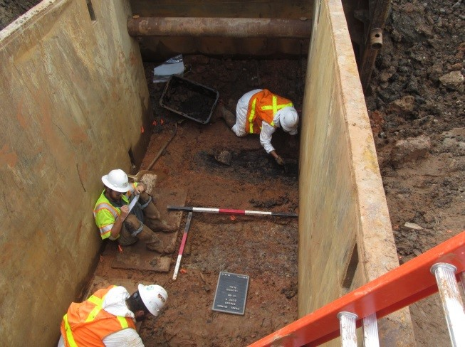 WSSI archeologists excavating and recording burials in a deep trench box excavation on the site.