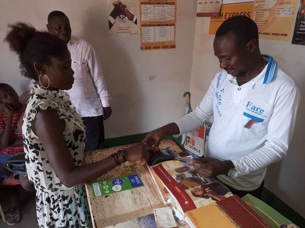 A new client making use of mobile money services being rolled out in rural areas in Kongo Central.