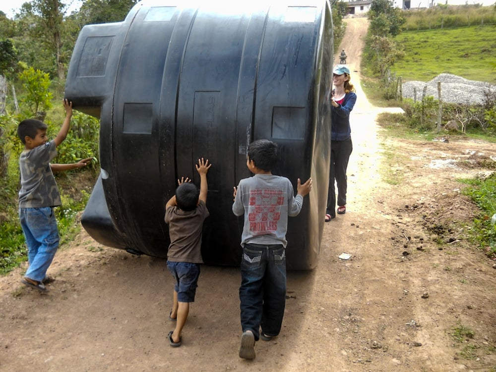 Children of Dulce Vivir playfully helping to roll septic tank into location with Peace Corp translator Joanna Miller guiding.