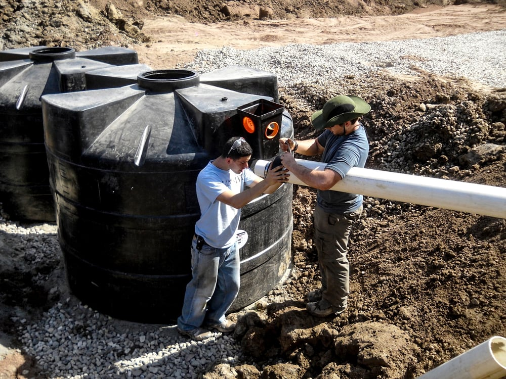 EWB students Daniel Gerges and Nick Oberti connecting sewer pipe to septic tanks.