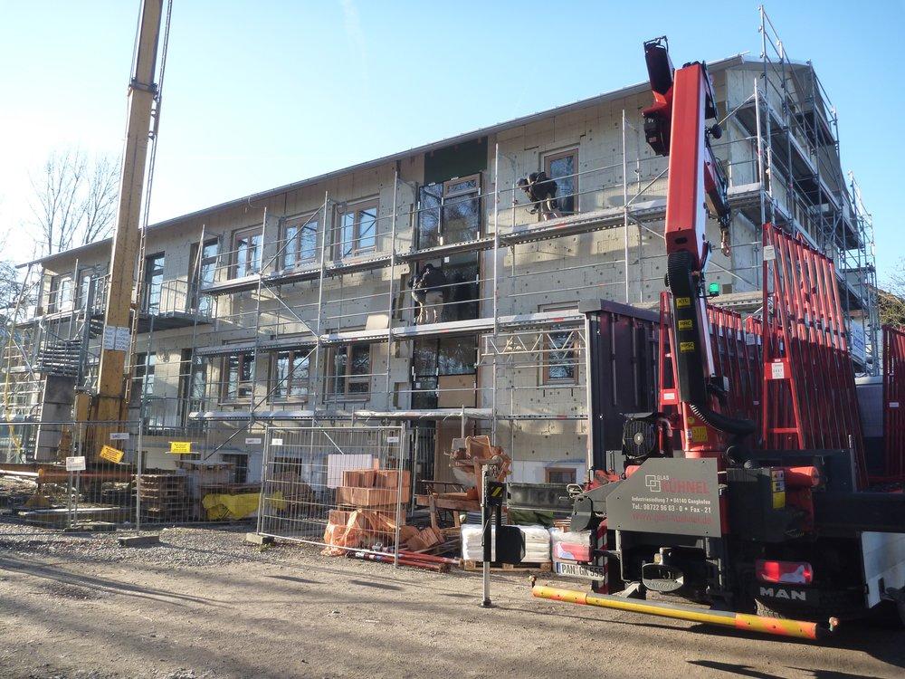 Die neue Treppenhausfassade wird eingebaut.
